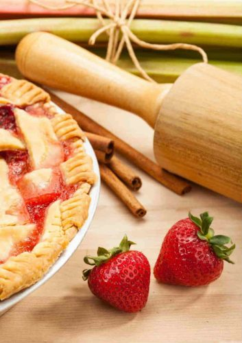 Rhubarb strawberry pie and wooden rolling pin fresh strawberries and four cinnamon stix