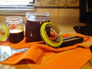 two glass jars with barbecue sauce in them, jars have green sealing rings all on an orange towel and barbecue utensil alongside