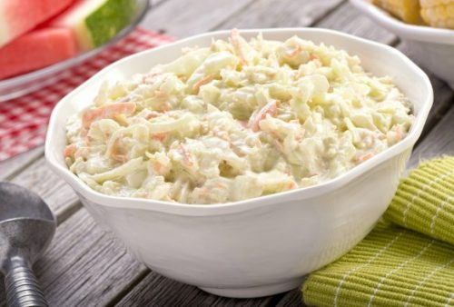 cabbage and carrot coleslaw with mayonnaise in large white bowl with red gingham checked cloth and green napkin