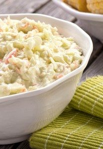 creamy homemade coleslaw with carrots, onion on a wooden table with a green napkin