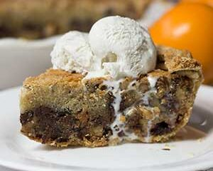side view of slice of chocolate chip pie, ice cream on top dripping down the side of the pie on a white plate orange in background