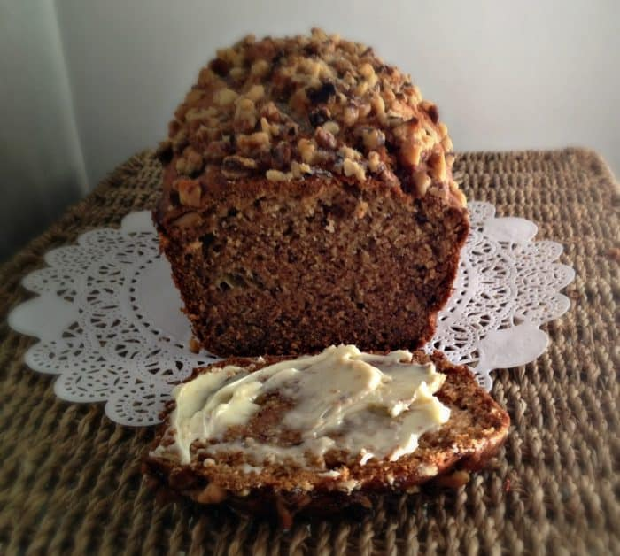 banana bread with slice in front slathered with butter on a white paper doily