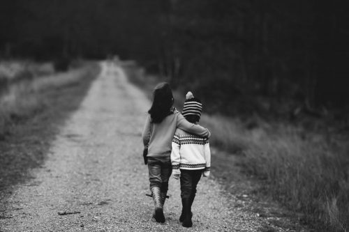 black and white photo of two children arm in arm walking down a country road
