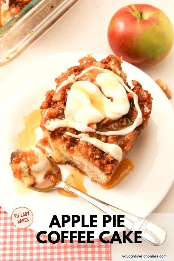 slice of apple pie coffee cake with white icing on white plate with spoon and apple to the side