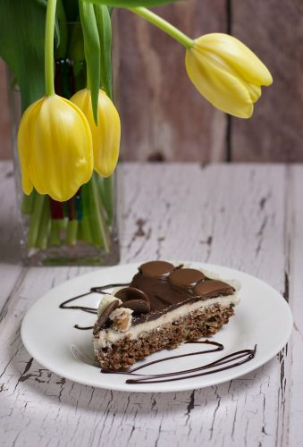 chocolate, coconut cream filled nanaimo bar pie on a white dessert plate with yellow tulips in a glass vase