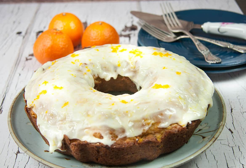 orange cranberry bundt cake covered with orange glaze, orange zest, three oranges in the background, blue plates and two forks and cake server