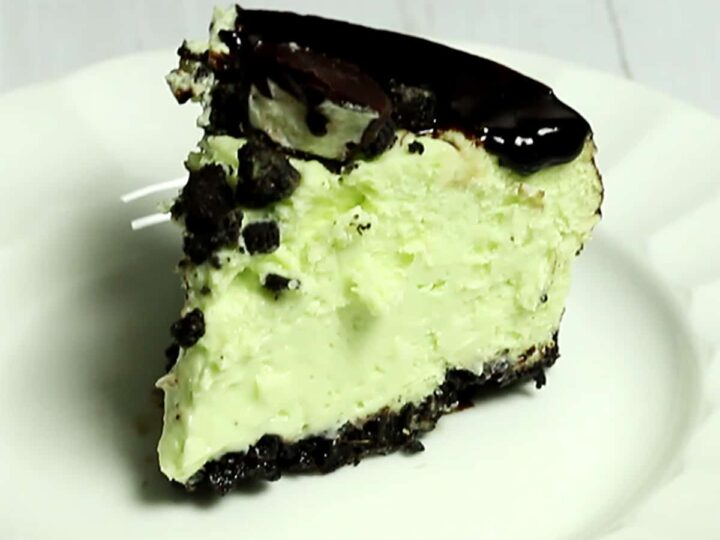 slice of instant pot mint chocolate cheesecake with dark chocolate ganache on a white plate
