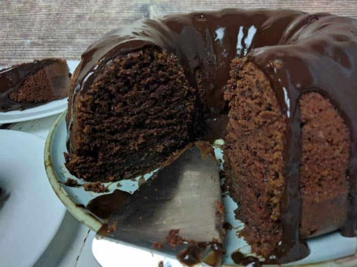 feature image of chocolate bundt cake shows rich texture of the cake topped with hot water chocolate frosting on a blue plate with cake server