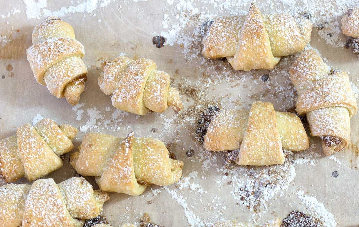 rugelach cookies with powdered sugar cooling on parchment paper