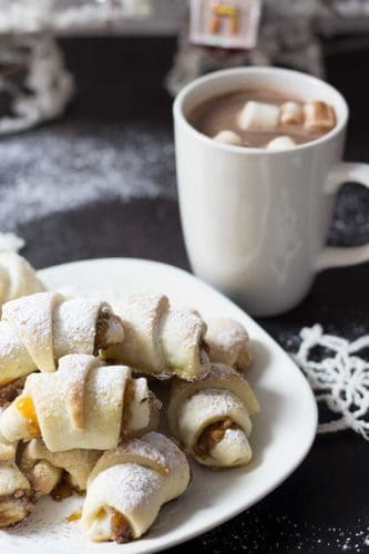 winter rugelach cookies on white plate with white mug of cocoa and mini marshmallows and crocheted snowflake in background