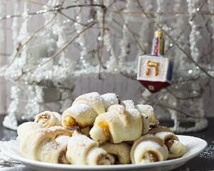 apricot jam rugelach cookies on a white plate in front of a white decorative tree with a dreidel ornament