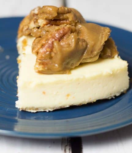 generous slice of eggnog cheesecake topped with pralines and brown sugar on a dark blue plate