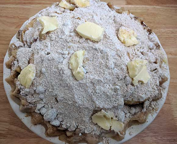 dutch apple pie with streusel topping and butter ready to bake