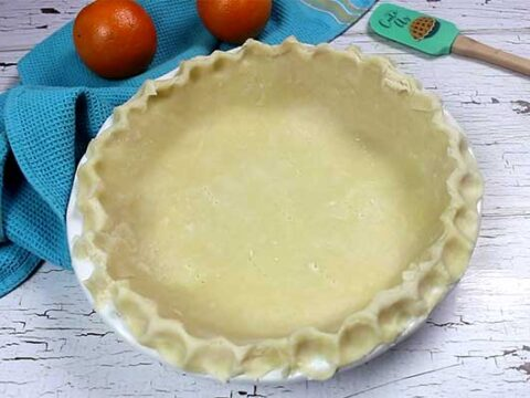 pie crust in white pie plate ready to bake, perfect flaky pie crust