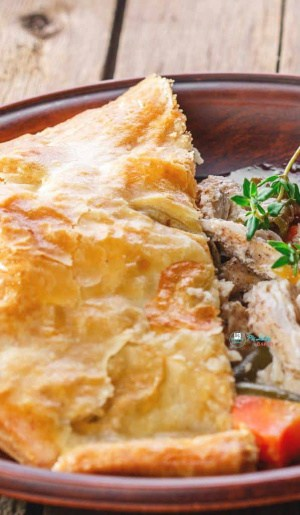 close up image of puff pastry Chicken Pot Pie with serving removed on a brown plate and brown fork