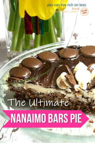 nanaimo bars pie in clear glass pie plate, slice cut from pie with yellow tulips in background white lettering on a pink arrow