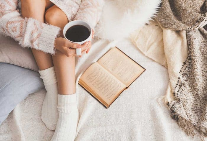 image shows woman with white socks on a bed of white sheets, pink blanket, holds a cup of black coffee and has a journal in front of her.