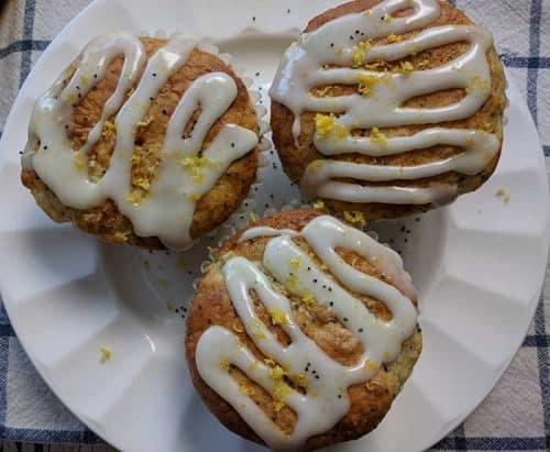 three lemon poppy seed muffins on a white china plate