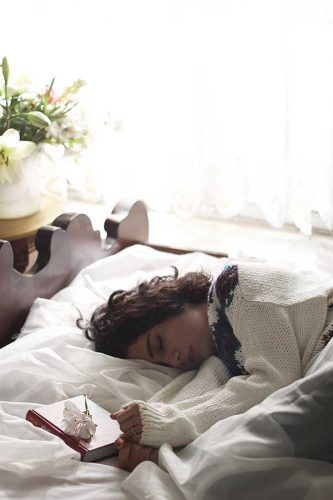 young woman sleeping with a white sweater on, white linens, and book closed with white flower on the book and a white vase of flowers in the background with sun streaming in the window