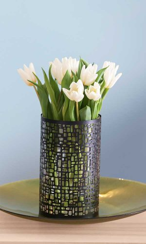 white tulips in a black mosaic vase on a gold glass dish