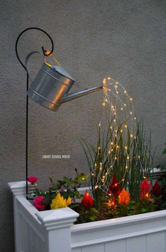 metal watering can on a black iron hook staked into a flower box with fairy lights coming out of the spout