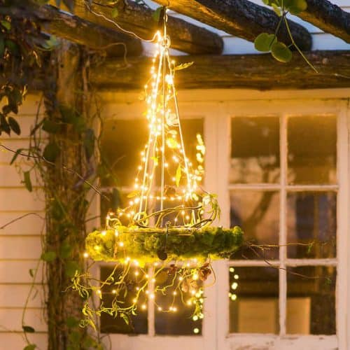 backyard chandelier, with circle of moss, frame is covered in fairy lights and hung from a gazebo, in front of a window, and vines growing on gazebo