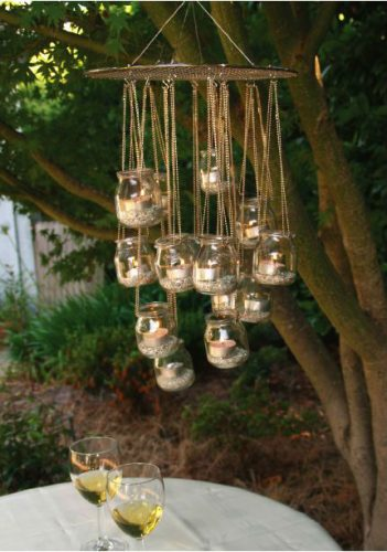 mini glass gloves held up by chains hanging from a tree