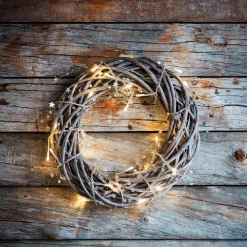 grapevine wreath hanging on a barn wall with fairy lights wrapped around it