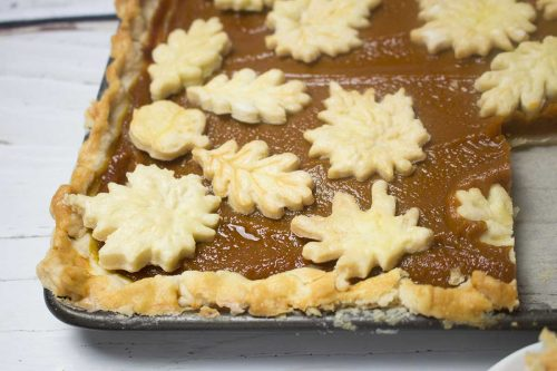 baked pumpkin slab pie shows slice removed