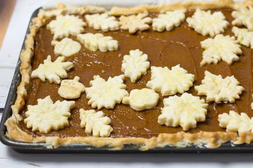 overview of pumpkin slab pie shows pie crust leaves on top of pumpkin filling