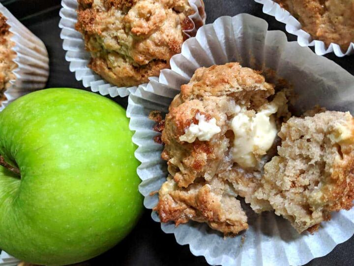 green apples with freshly baked apple muffin in muffin wrapper with melted butter on top more muffins in the background