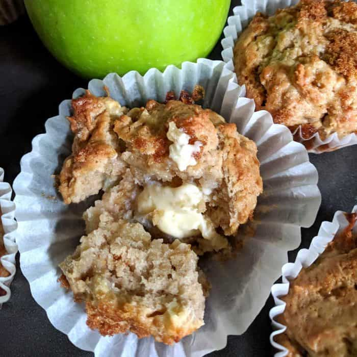 apple muffin, broken open with butter melting inside, top of image shows extra muffins and green apple