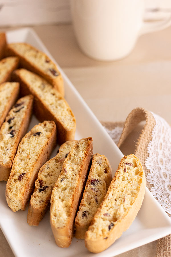 cranberry almond biscotti on a white square plate with jute and lace ribbon, coffee mug in background