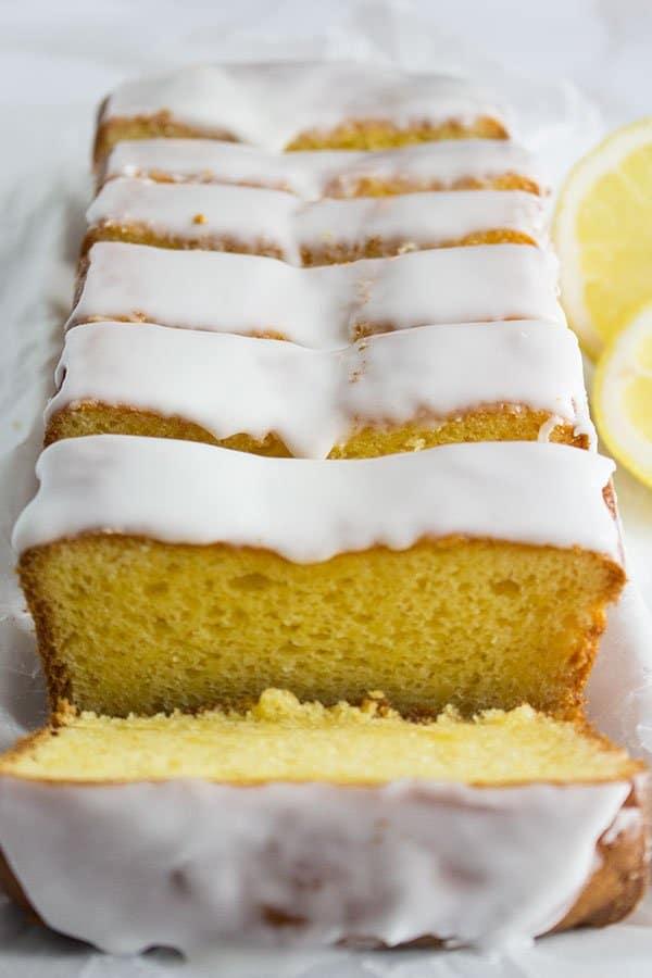 lemon loaf pound cake slices close up with lemon glaze frosting, box cake mix hacks
