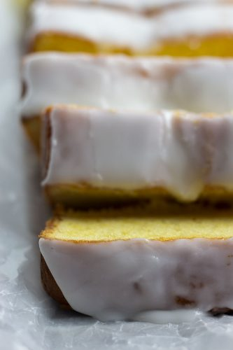 emon loaf cake with white glaze icing, sliced on a white plate with lemons on the side,