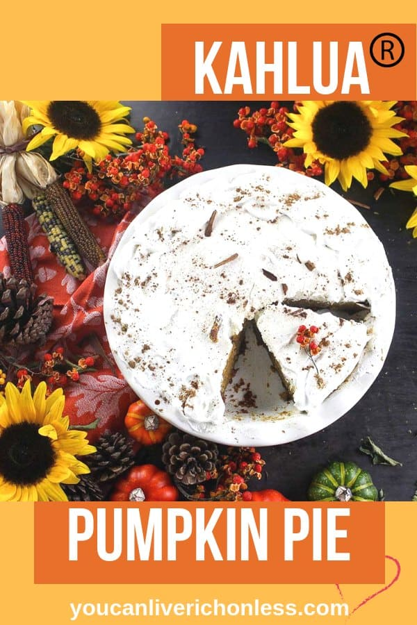 overhead shot of kahlua pumpkin pie with slice cut surrounded by harvest flowers
