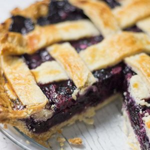 whole razzleberry pie with slice removed in a clear glass pie plate