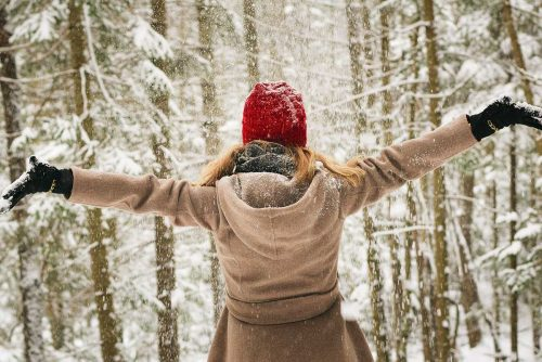 woman with camel coloured coat and red knitted hat outdoors with arms outstretched in front on snow covered trees