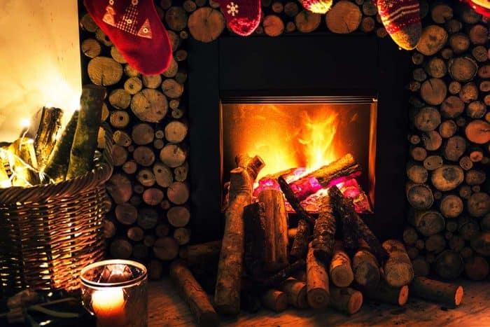 festive fireplace with decorated mantel, logs stacked to the left and a candle in the foreground
