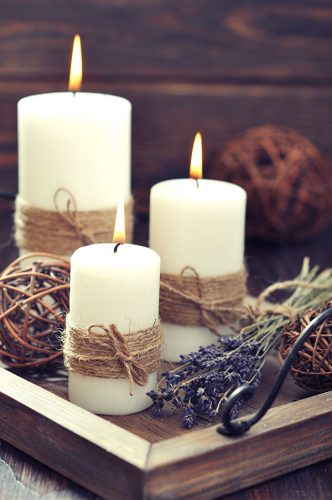 three white candles wrapped in jute on a wooden tray with lavender sprigs how to survive winter