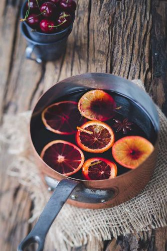 copper pot on wooden table and burlap cloth under pot with mulled wine, slices of oranges and spices floating on top.