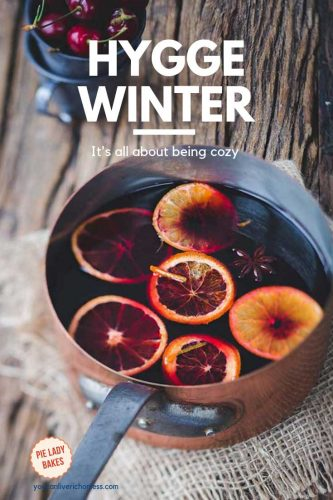 hygge winter in white text on image that shows copper pot full of mulled wine, sliced oranges floating on top, surface is barn board