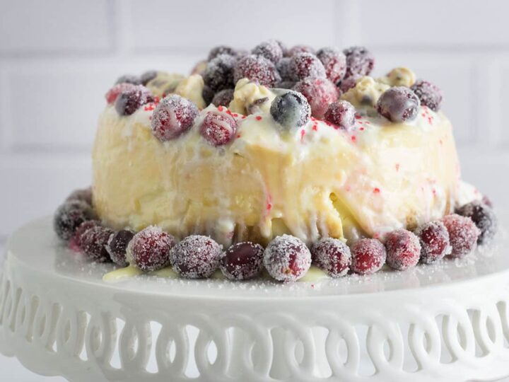 white chocolate cheesecake with sugared cranberries on white cake plate with white background