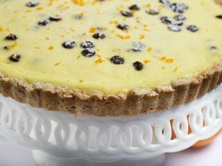 ricotta pie on white cake plate with scalloped edging and orange by pedestal to the right