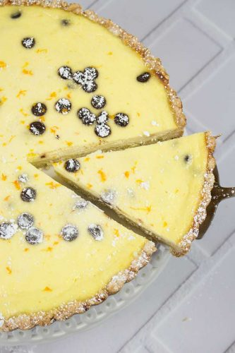 sweet custard pie with chocolate chips and orange with slice cut and pie server underneath