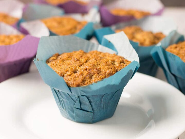 spice cake muffins in blue and purple baking wrappers with a white dessert plate