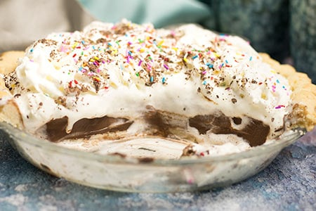 chocolate pudding pie mounded with whipped cream and multi coloured sprinkles with half of the pie already removed, shows bottom of glass pie plate