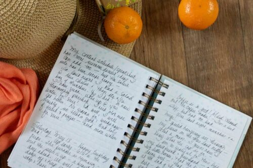 open journal on a wooden table with orange shawl, straw hat and two mandarin oranges in the background. open pages have writing on them