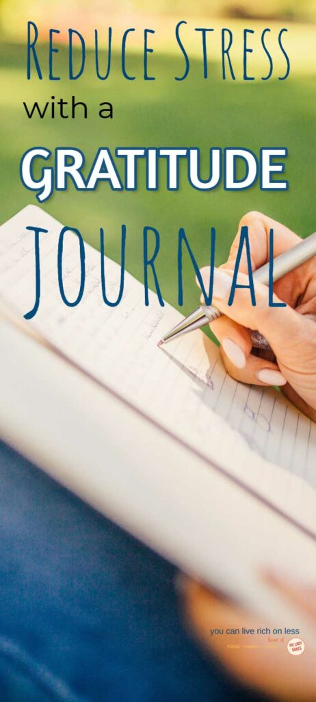 image of someone writing in a journal outdoors wearing blue pants caption says Reduce stress with a gratitude journal
