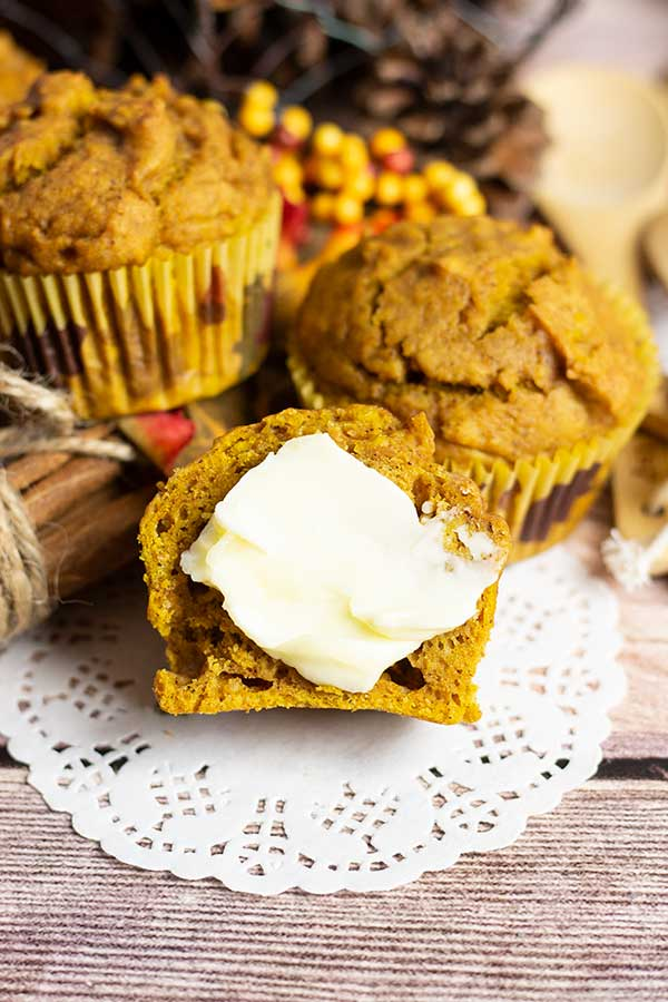 pumpkin muffin with butter and other muffins in the background on a white paper doily